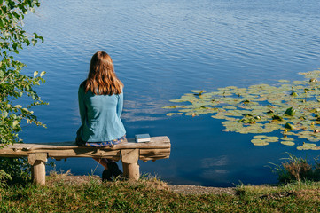 teen girl reading book outside by pond