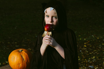 A little girl dressed as a bat eating a toffee apple.