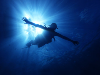 Person Swimming Underwater with Sun Rays Behind Wall mural