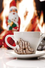 Coffee cup and a gingerbread cookie shaped as a little rocking horse, chimney fire and chocolate Santa at back