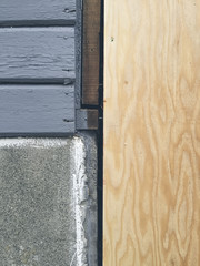 Plywood covering old wood siding and window on house exterior