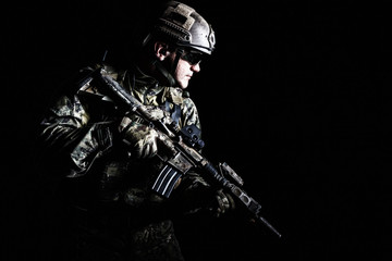 Half length low angle studio shot of special forces soldier in field uniforms with weapons, portrait on black background. Protective goggles glasses are on