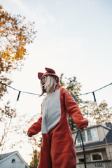 Cute girl in fox costume jumping on trampoline