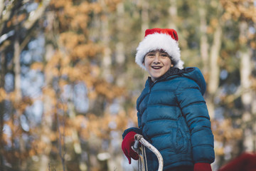 Boy with Santa hat standing in the forest.