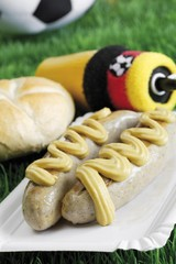 Two bratwurst sausages with mustard and bread roll on a football field, German national colours