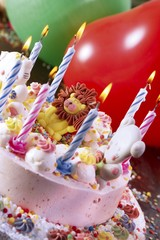 Children's cake with an icing lion, lit candles and a balloon - children's birthday party