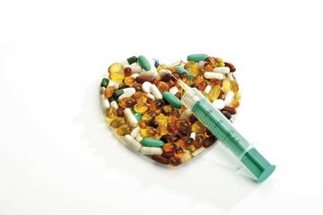 Pills formed in the shape of a heart, syringe