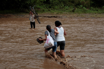 Local residents cross a river flooded by heavy rains by Tropical Storm Nate in Nandaime