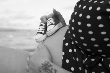 Ritratto di una donna in cinta con delle scarpe da bambino appoggiate sulla pancia
