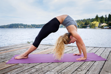 Beautiful young woman practicing yoga near a lake