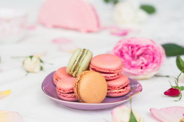 macarons and roses on an embroidered cloth