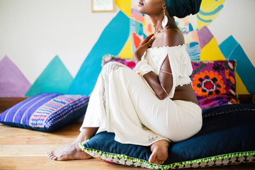 Young african woman sitting on the cushion floor in exotic colorful design space