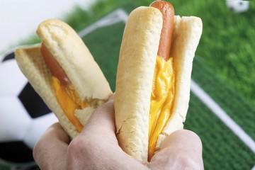 Hand holding two hot dogs, football and pitch