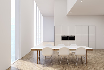 White and wooden kitchen with a table, ovens