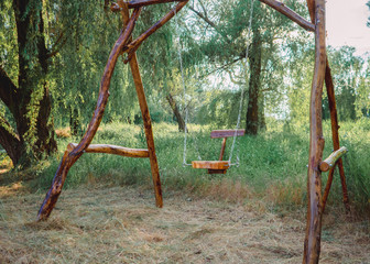 A wooden swing in the park. Eco-friendly materials in green environment