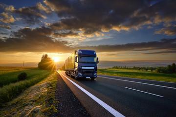 Fotobehang - Blue truck driving on the asphalt road in rural landscape at sunset between dark clouds