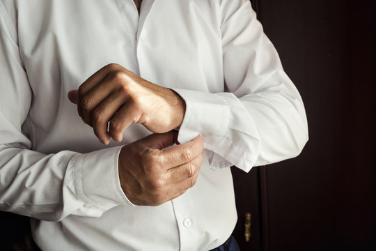 Businessman dress shirt. The man in the white shirt in the window dress cufflinks. Politician, man's style, Businessman buttoning his shirt,male hands closeup, American, European businessman