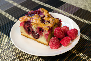 Cherry sponge cake with berries fresh raspberries