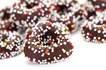 Fudge rings covered in chocolate and sprinkles or hundreds-and-thousands, sweet Christmas tree decoration