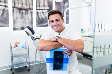 Portrait of handsome smiling dentist holding  x-ray image of his patient.