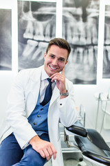 Portrait of handsome smiling dentist. He is standing in his dentist office. X-ray image on background.