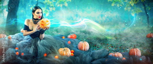 Halloween witch with a carved pumpkin and magic lights in a dark forest