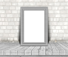 3D blank silver picture frame on a wooden table leaning against a brick wall