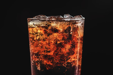 close up ice cola in glass and bubble soda on black background