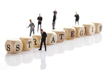 Strategie, German for strategy, written with wooden letters and miniature manager figures
