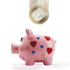 Euro coin falling into pink piggy bank (composing shot)