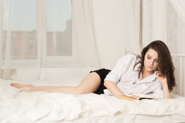 girl is reading a book in bed
