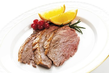 Three slices of goose-breast, red-currants and orange slices