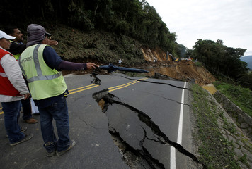 Workers of the National Emergency Commission check a highway that connects with the south of the country that was collapsed by Storm Nate in Casa Mata, Costa Rica
