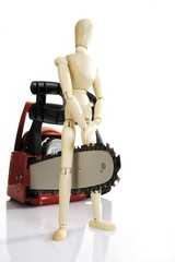 Chainsaw and wooden figure - symbol for accident risk