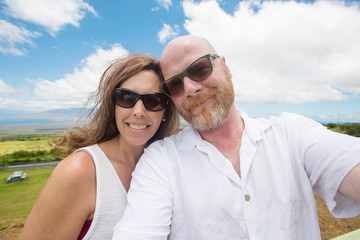 Middle aged couple with heads touching under bright blue sky
