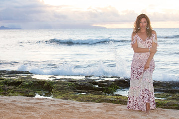 Beautiful woman wearing prettyy dress at the ocean during sunset
