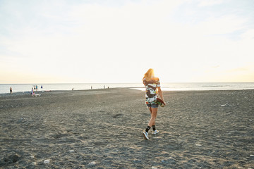 Girl walking on the sea shore in sunset