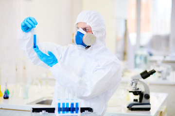 Confident chemist wearing coverall and respirator studying test tube with toxic liquid, interior of modern laboratory on background
