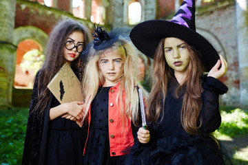 Group of friendly witches in halloween costumes asking you for a treat