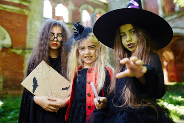 Gloomy little witch and her friends frightening you on halloween day