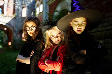 Frightening girls leaning against wall of building on halloween evening outdoors