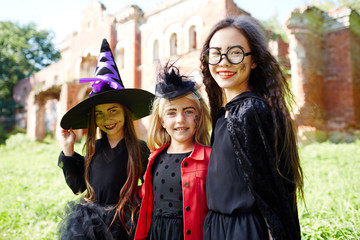 Group of happy halloween kids in carnival attire enjoying celebration