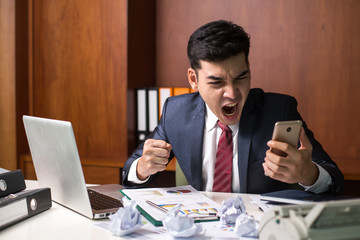 Businessman angry and furious with a Smartphone at office, Man wirking with Angry Emotion.