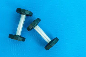 Fitness background with dumbells on blue mat topdown view.