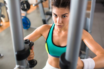 Confident athletic woman looking at camera while having intensive training on butterfly machine at modern gym, waist-up portrait