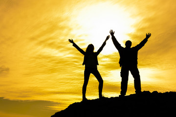 Two people between clouds Full length silhouette of happy couple stand together on peak of a mountain with hands raised up, sunset and ocean. Man and woman on top mountain look at beautiful night