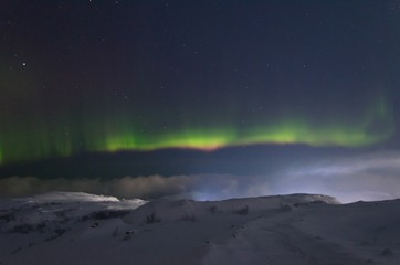 The snow covered the hills and in the sky the stars and the aurora borealis.