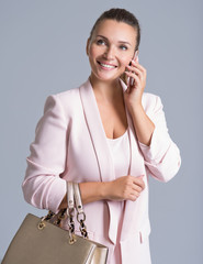 Happy beautiful woman holds handbag and mobile