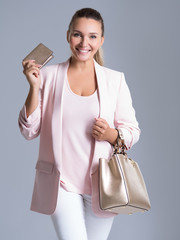 Happy beautiful woman with handbag and wallet in shopping