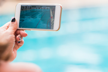 woman hand holding her phone recording swimming pool activities